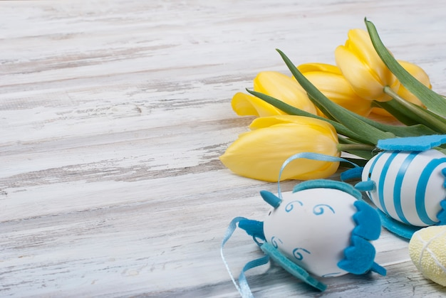 Bouquet of yellow tulips and chikken easter eggs with a blue ribbon on a wooden background