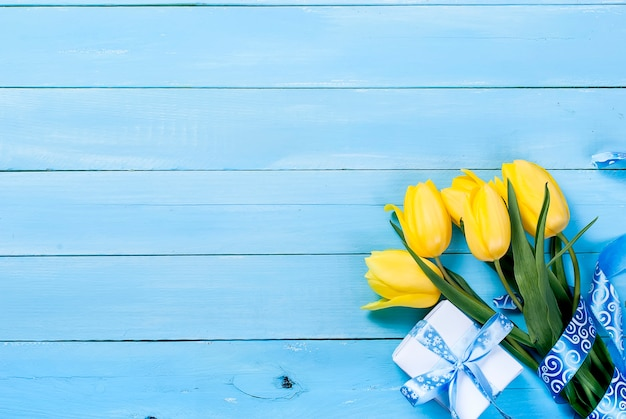 Bouquet of yellow tulips and a gift with a blue ribbon on a blue wooden background