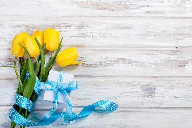 Bouquet of yellow tulips and a gift with a blue ribbon on a wooden background
