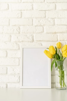 Bouquet of yellow tulips in a glass vase and blank photo frame on a white brick wall background. mock up design