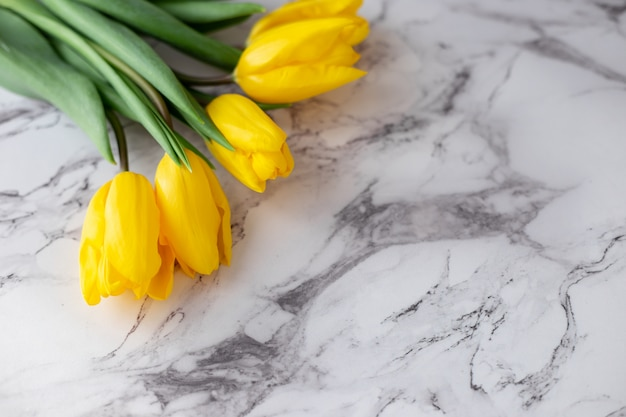 A bouquet of yellow tulips lies in the upper left corner on a granite