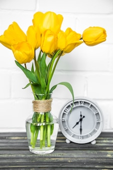 Bouquet of yellow tulips and a retro clock