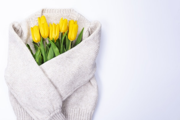 Bouquet of yellow tulips on white background knitted sweater with place for text, top view, bouquet of yellow tulips for women's day, concept of spring flowers
