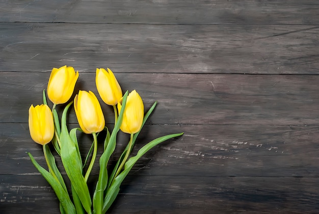 Bouquet of yellow tulips with a yellow ribbon on a wood
