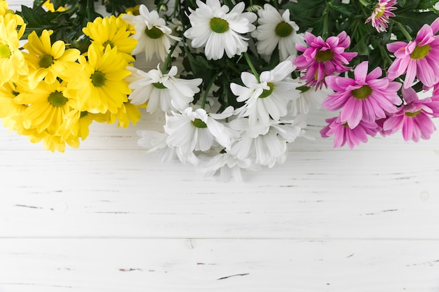 Bouquet of yellow; white and pink daisy flowers on white wooden textured background
