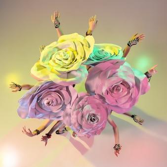 꽃다발. 그라데이션 벽에 네온 불빛에 거대한 꽃 모자와 젊은 여성 댄서. 우아한 모델, 여성의 춤, 포즈. 카니발, 뷰티, 모션, 개화, 봄 패션의 개념.