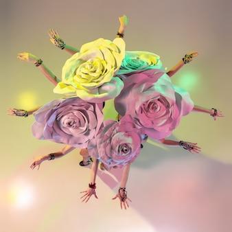 꽃다발. 그라데이션 벽에 네온 불빛에 거대한 꽃 모자와 젊은 여성 댄서. 무료 사진