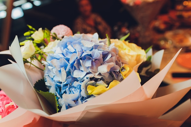 Bouquets of flowers on the floor in front of a flower shop with lilies, sunflowers, carnations, statices, and more.