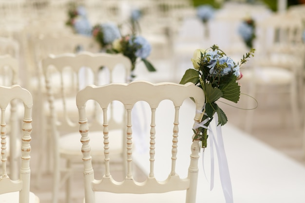 Bouquets of greenery and blue hydrangeas pinned to the white cha
