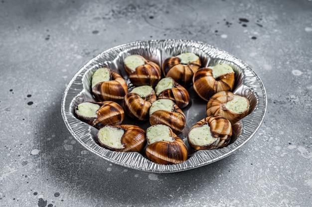 부르고뉴 에스카르고 달팽이와 마늘 버터. 회색 배경입니다. 평면도.