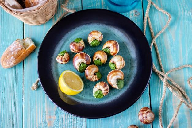 Bourguignonne snail with lemon blue wooden surface