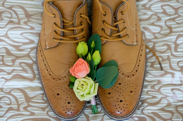 Boutonniere lie on shoes