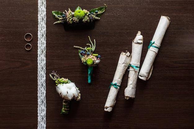 レース付きの茶色のテーブルの上に横たわる綿で作られたブートニエール、古い羊皮紙の巻物