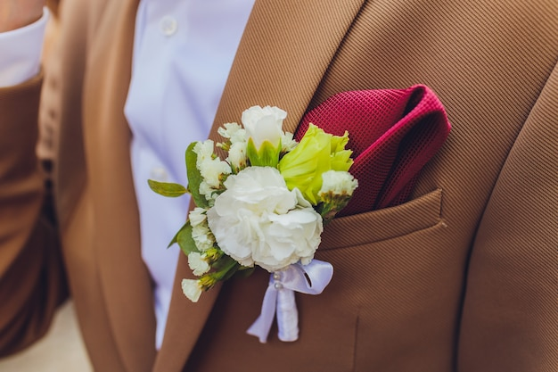 Boutonniere peonies flower on blue suit jacket of wedding groom close-up.