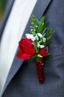 Boutonniere of red roses and greenery attached to the gray suit groom