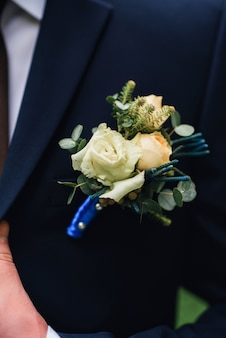 Boutonniere with a white rose on the lapel of the groom's blue jacket