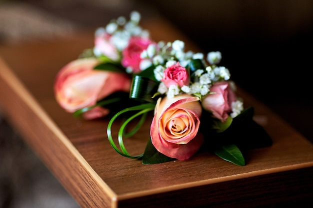 Boutonnieres made of pink roses and greenery lie on the table