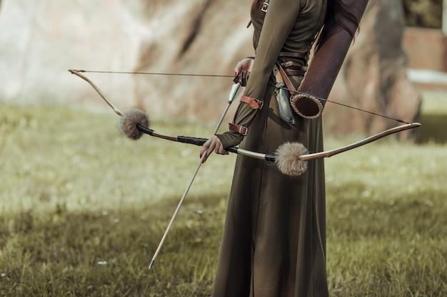 Лук и стрела крупным планом, женский лучник.