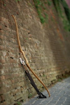Bow and arrows leaning on brick wall in old town.