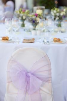結婚式の装飾の弓の椅子。休日テーブルの前。