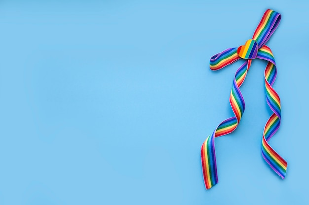 Bow from a rainbow ribbon with a rainbow heart on a blue background. lgbt concept