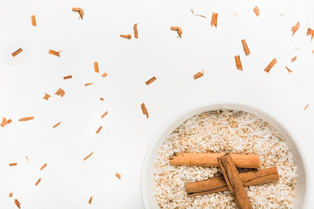 Bow of rice with cinnamon sticks on white background