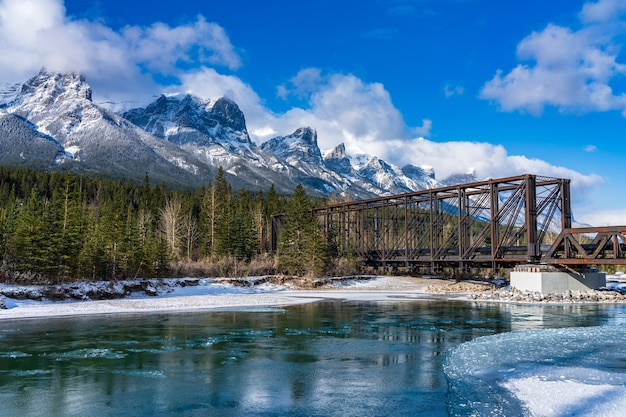 Bow river in winter sunny day. snow capped mount rundle mountain range in background.