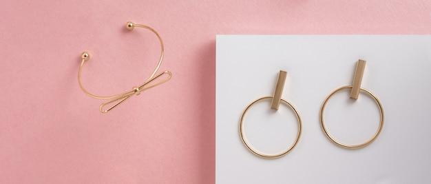 Браслет в форме банта и золотые серьги на белой и розовой поверхности