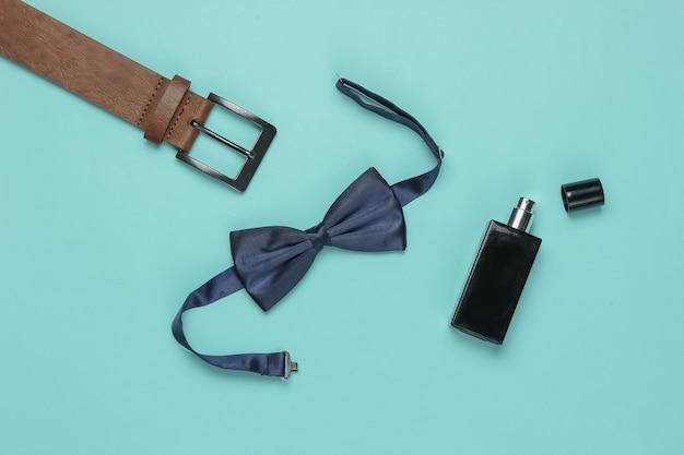 Галстук-бабочка, пояс, флакон духов на синем фоне. мужские аксессуары, мужской деловой комплект. формальный стиль, подготовка к свадьбе.