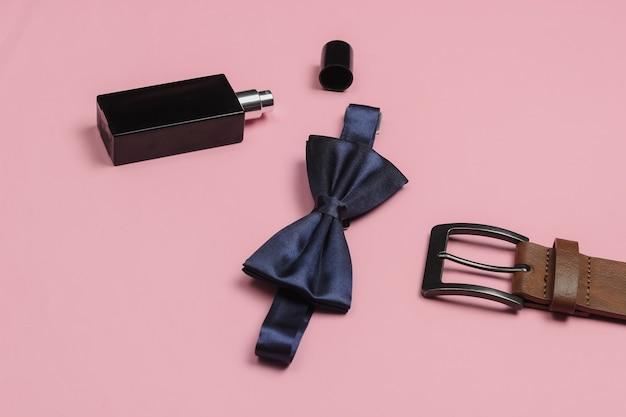 Галстук-бабочка, пояс, флакон духов на розовом фоне. мужские аксессуары. формальный стиль, подготовка к свадьбе.