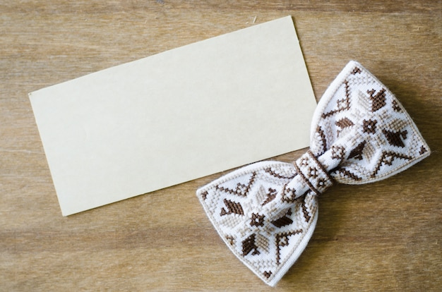 Bow tie and empty card on wooden background.