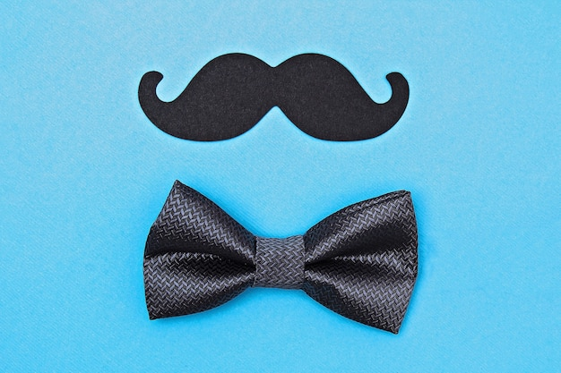 Bow tie and mustache on blue surface
