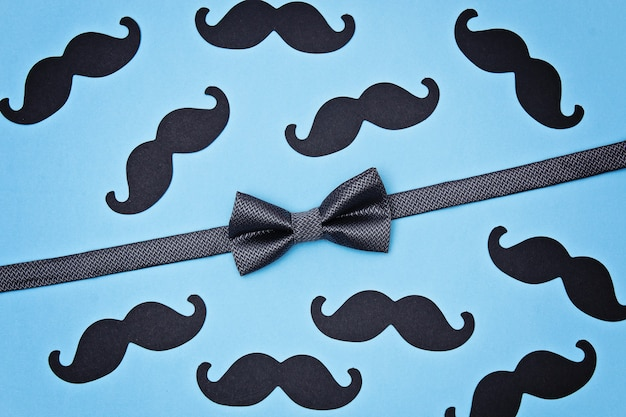 Bow tie and mustaches on blue surface