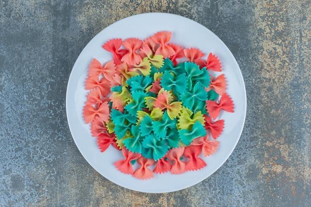 Макароны с галстуком-бабочкой в тарелке, на чайной башне, на мраморной поверхности.
