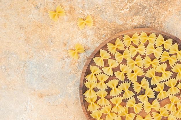 Макароны с галстуком-бабочкой на деревянной тарелке, на мраморе.