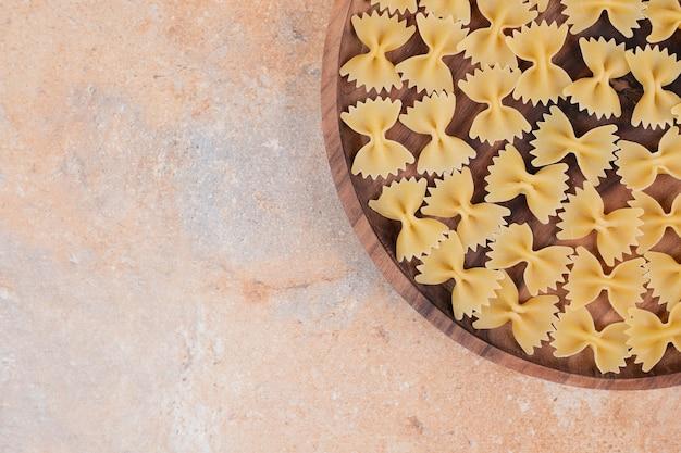 大理石の背景の木製プレートに蝶ネクタイパスタ。高品質の写真