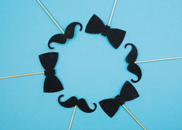 Bow ties and mustaches on wands in form of circle