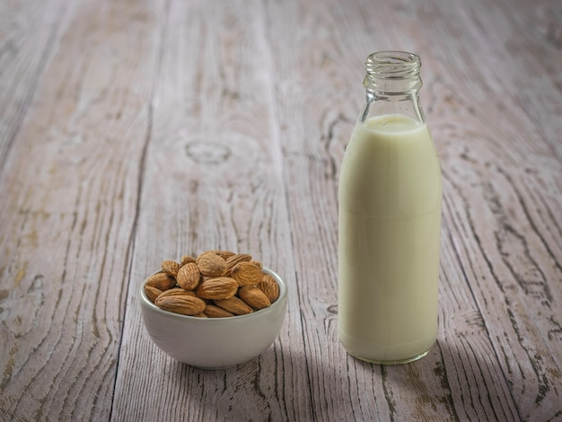 A bowl of almonds and a bottle of almond milk on a wooden table. vegetarian milk.