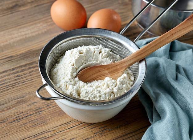 生地を作るための台所のテーブルのストレーナーのボウルと小麦粉