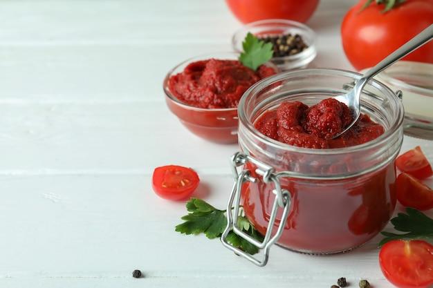 그릇과 재료와 흰색 나무 배경에 토마토 페이스트와 항아리