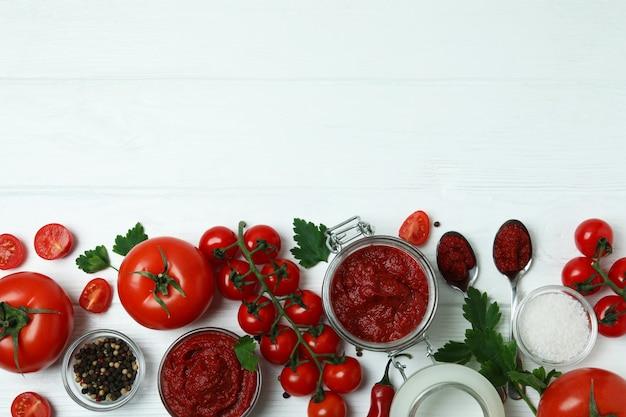 그릇과 재료와 흰색 나무 표면에 토마토 페이스트와 항아리