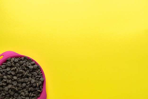 Bowl of animal feed on a yellow background. flat lay, top view. space for text.