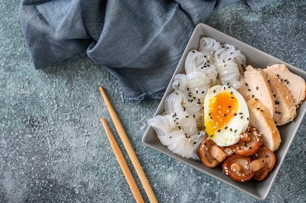 Bowl of asian food with konnyaku, slices of chicken breast, shiitake and soft-boiled egg