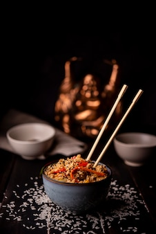 Bowl of asian food with rice and chopsticks