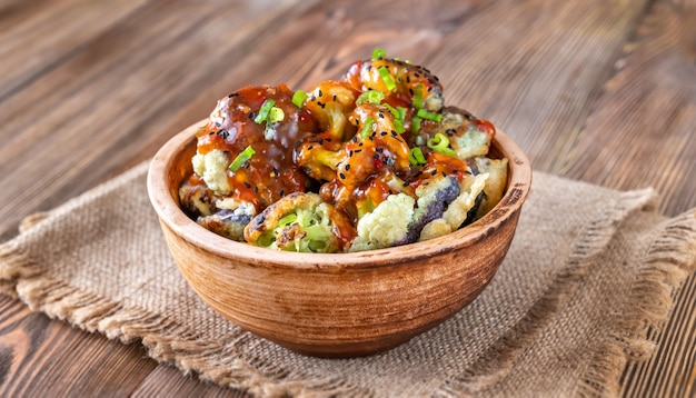 Bowl of asian fried cauliflower on rustic background