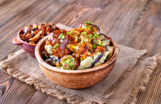 Bowl of asian fried cauliflower with sweet chili sauce