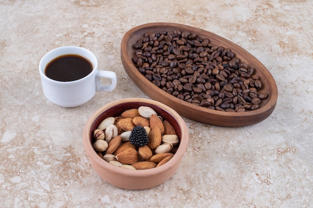 A bowl of assorted nuts, a tray of coffee beans and a cup of black coffee