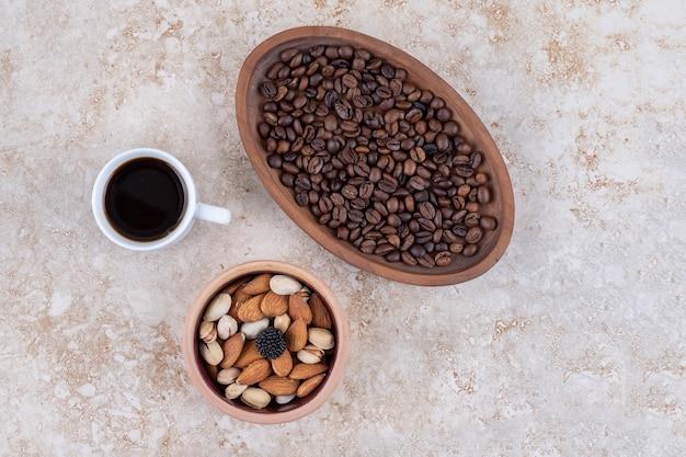 Una ciotola di noci assortite, un vassoio di chicchi di caffè e una tazza di caffè nero