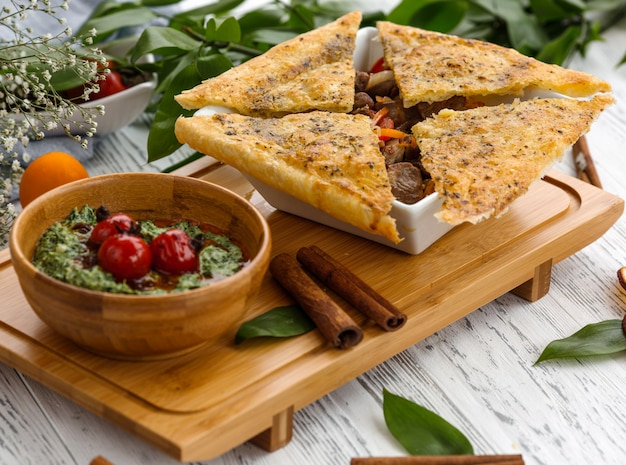 Bowl of azerbaijani roasted meat cooked with dried furits topped with crusty flatbreads