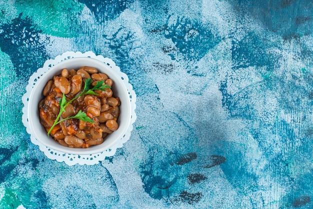Una ciotola di fagioli al forno su un sottobicchiere, sullo sfondo blu.
